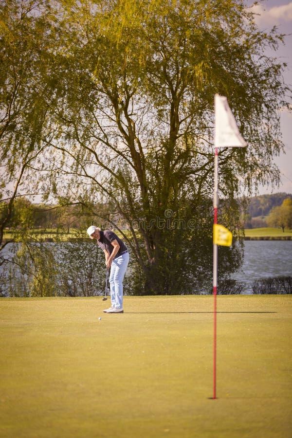 Giocatore di golf senior che mette sul verde fotografie stock