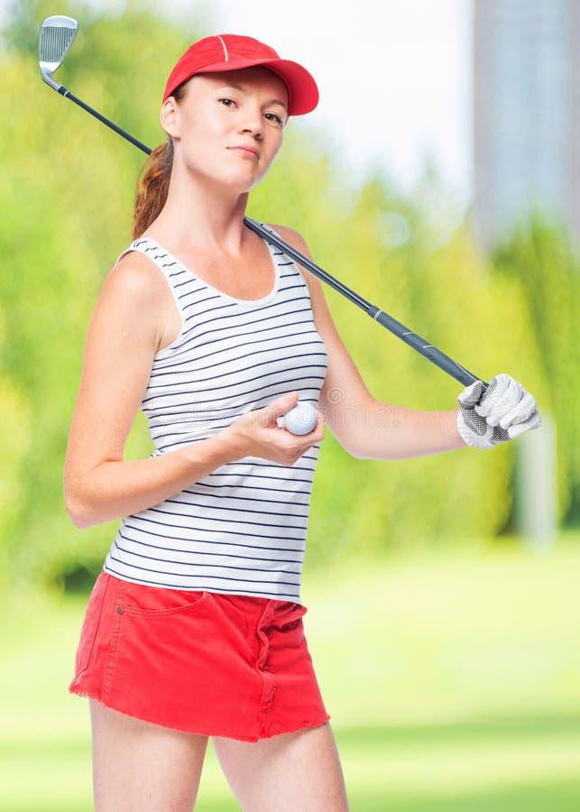 Giocatore di golf snello della sportiva con il bastone e la palla fotografie stock