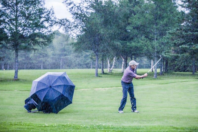 Giocatore di golf un giorno piovoso Swigning nel tratto navigabile immagine stock
