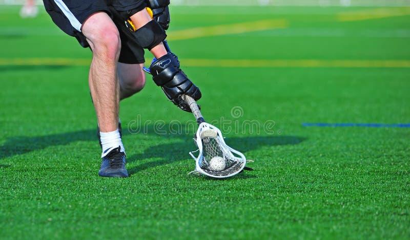 Giocatore di Lacrosse che scava in su la sfera fotografia stock libera da diritti