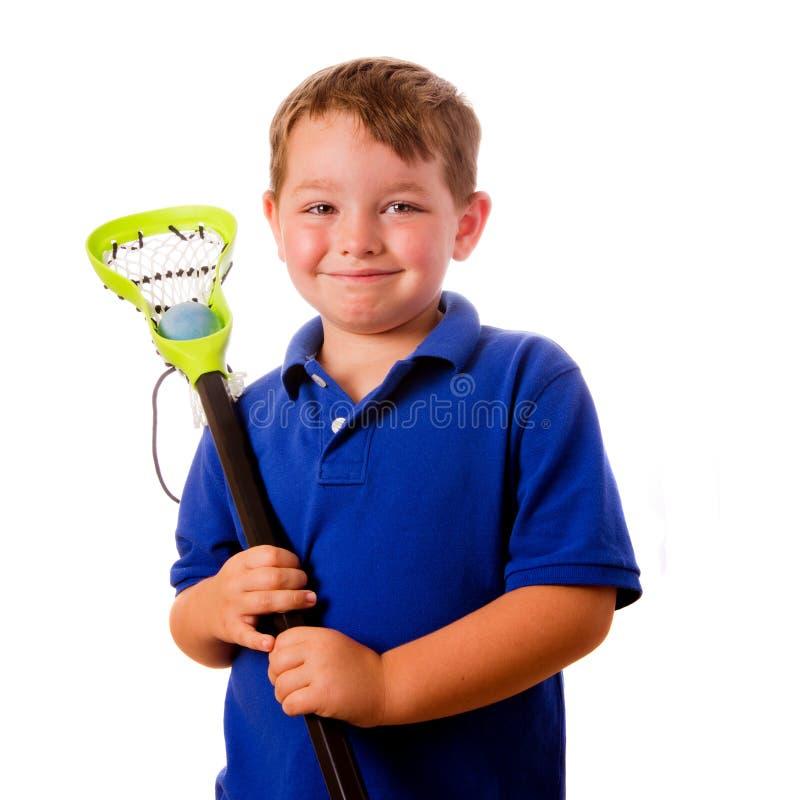 Giocatore di lacrosse del bambino con il suoi bastone e sfera fotografia stock
