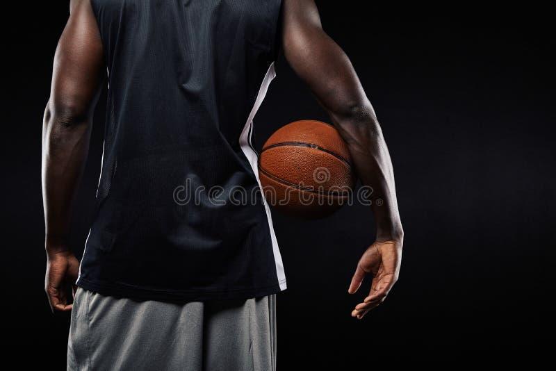 Giocatore di pallacanestro africano con una palla in suo braccio fotografia stock libera da diritti