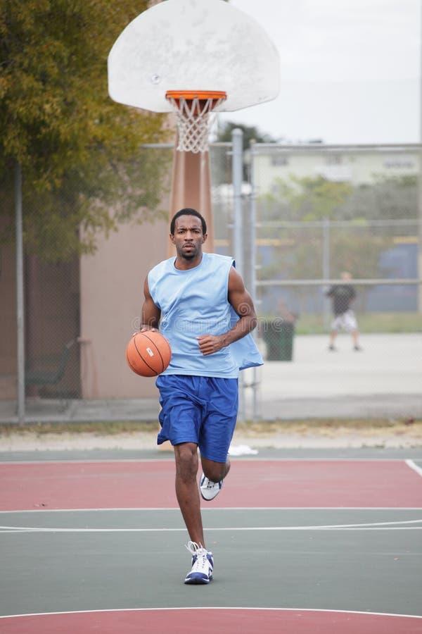 Giocatore di pallacanestro che esegue e che gocciola la sfera immagine stock libera da diritti