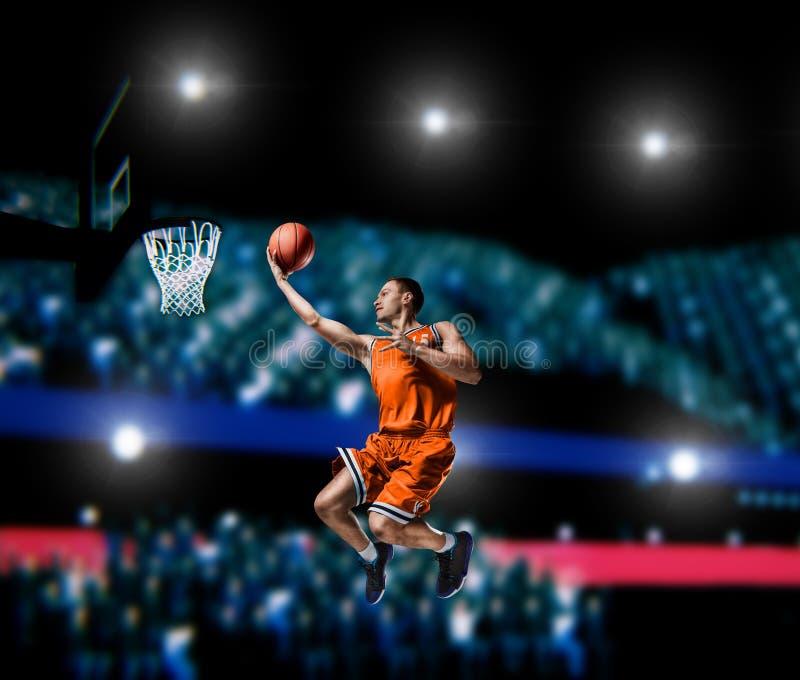 Giocatore di pallacanestro che fa schiacciata sull'arena di pallacanestro fotografie stock libere da diritti