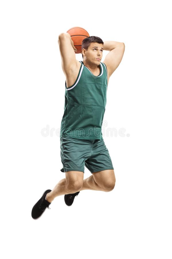 Giocatore di pallacanestro maschio nella fucilazione di azione con una palla e un salto fotografia stock
