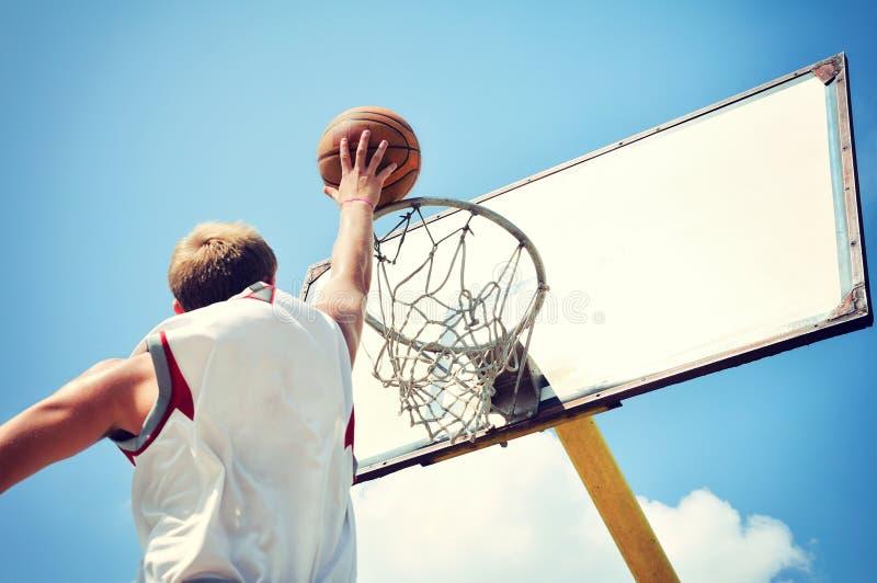 Giocatore di pallacanestro nel volo di azione alto e nel segnare fotografie stock