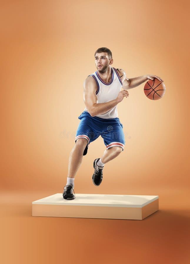 Giocatore di pallacanestro nell'azione su fondo arancio fotografia stock