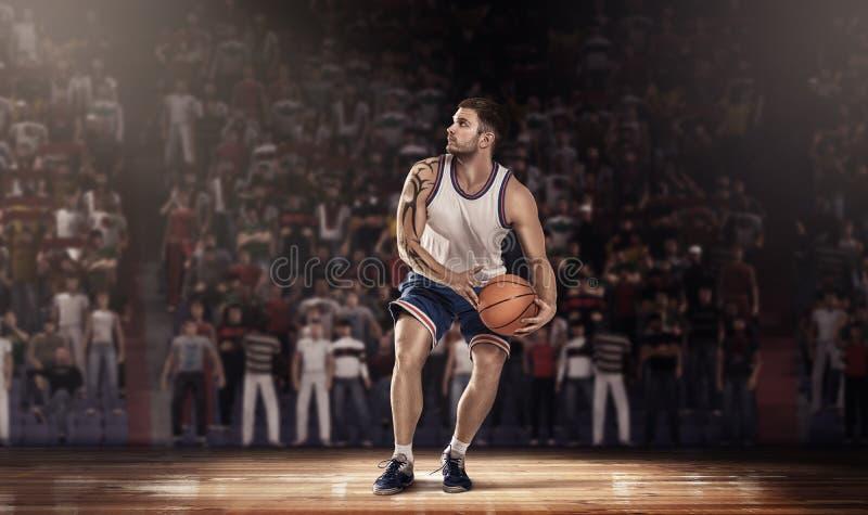 Giocatore di pallacanestro sul parquet con la palla nei raggi luminosi fotografia stock
