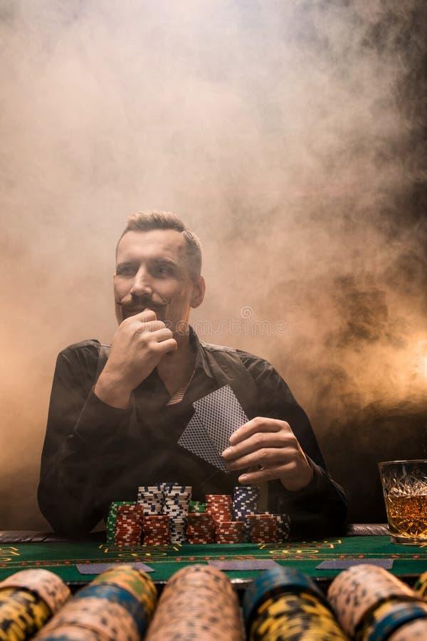 Giocatore di poker bello con due assi nelle suoi mani e chip che si siedono alla tavola del poker in una stanza scura in pieno de immagini stock
