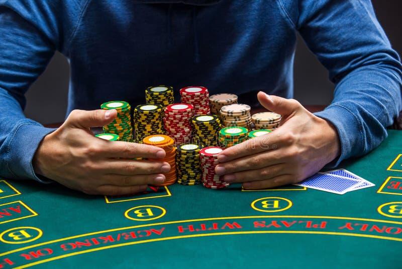 Giocatore di poker che prende i chip di poker dopo la conquista immagini stock libere da diritti
