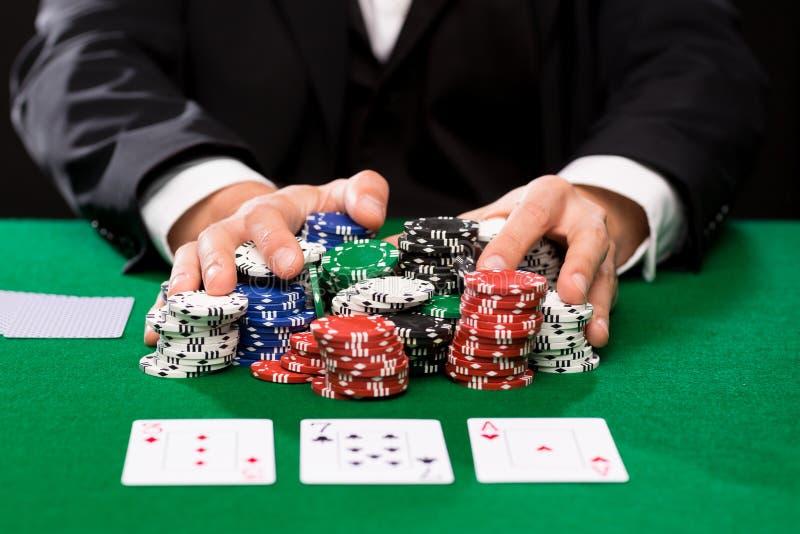Giocatore di poker con le carte ed i chip al casinò fotografia stock libera da diritti