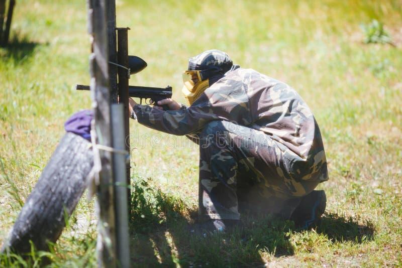 Giocatore di sport di paintball in uniforme e maschera con la pistola all'aperto fotografia stock