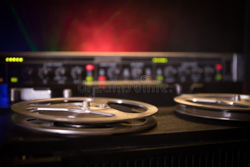 Giocatore e registratore bobina a bobina d'annata anziani su fondo nebbioso tonificato scuro Giocatore di registratore aperto del fotografia stock libera da diritti