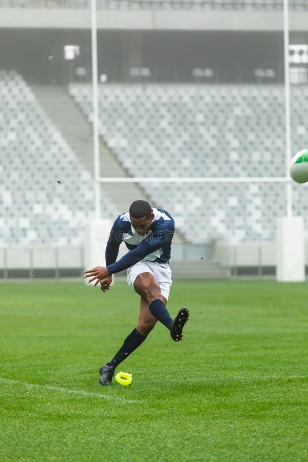 Giocatore maschio afroamericano di rugby che dà dei calci alla palla di rugby in stadio immagini stock libere da diritti