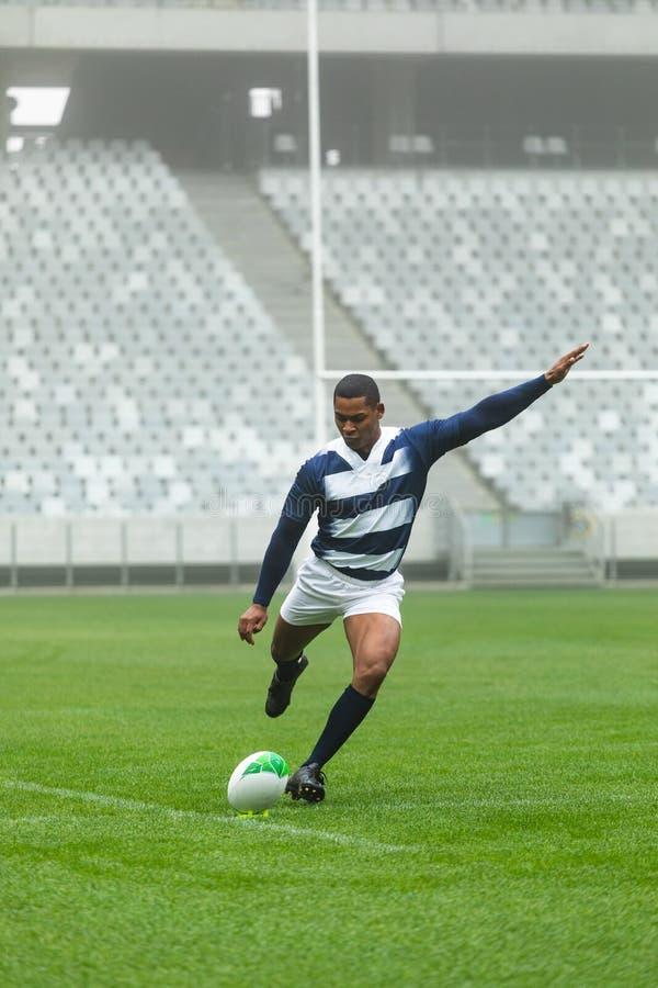 Giocatore maschio afroamericano di rugby che dà dei calci alla palla di rugby in stadio fotografia stock libera da diritti