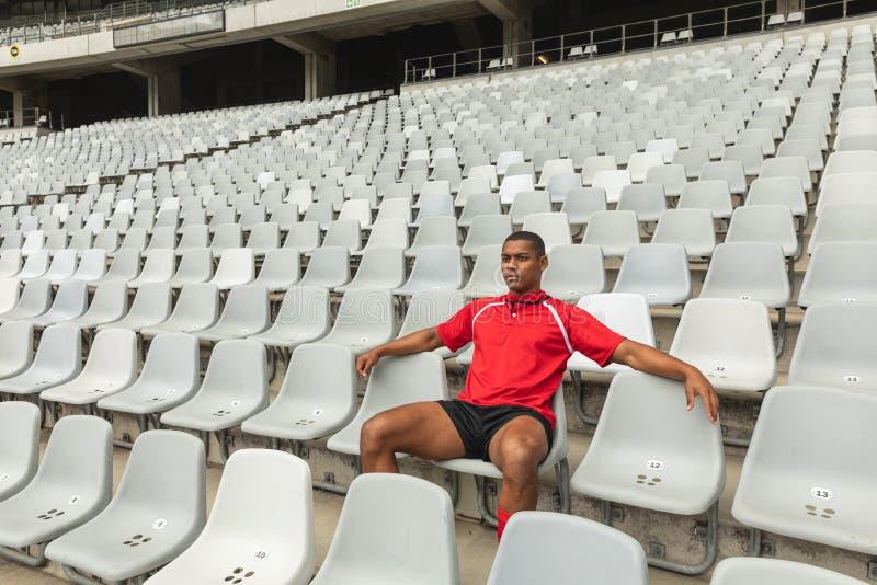 Giocatore maschio afroamericano premuroso di rugby che si siede da solo nello stadio fotografia stock libera da diritti
