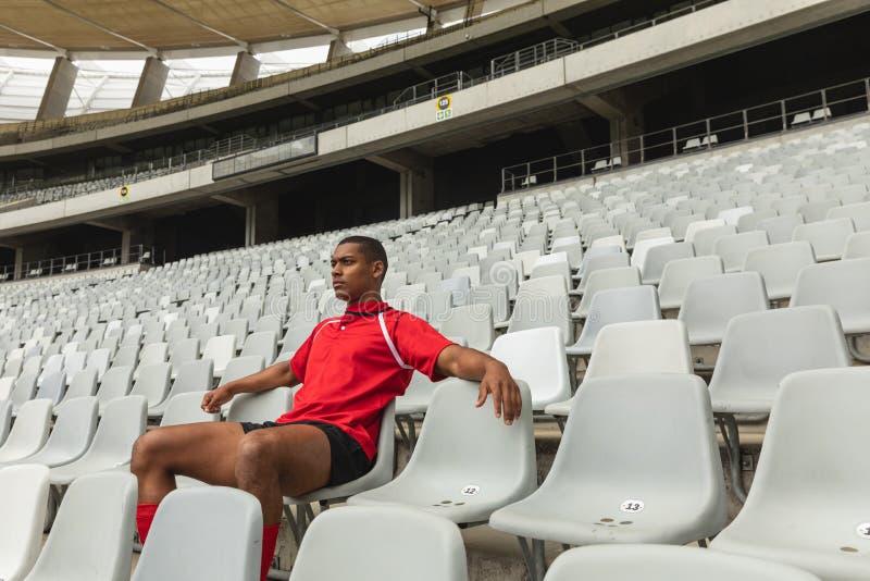 Giocatore maschio afroamericano premuroso di rugby che si siede da solo nello stadio immagini stock libere da diritti
