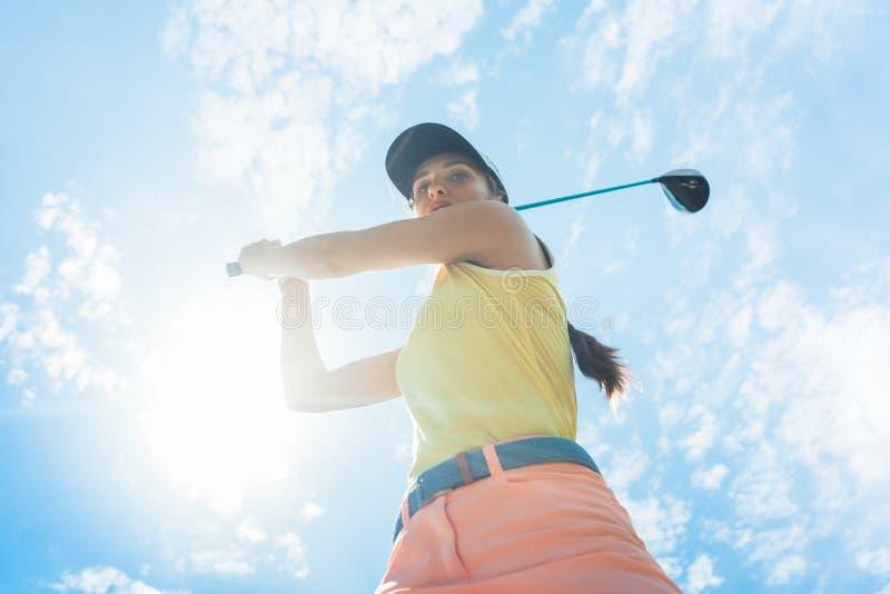 Giocatore professionale femminile che sostiene il club del ferro mentre giocando immagini stock
