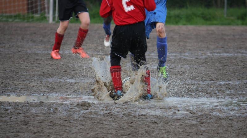 Giocatori dei bambini durante la partita di calcio in un campo da gioco in pieno fotografia stock libera da diritti