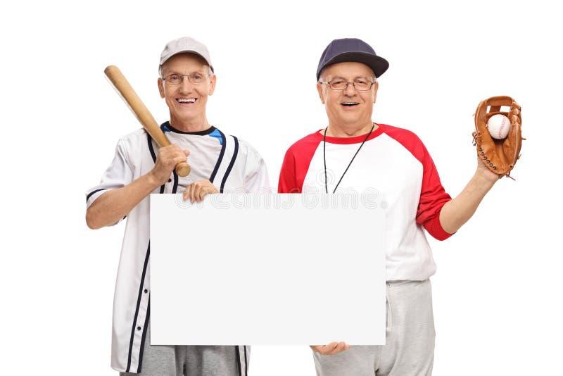 Giocatori di baseball pensionati che tengono un segno fotografia stock