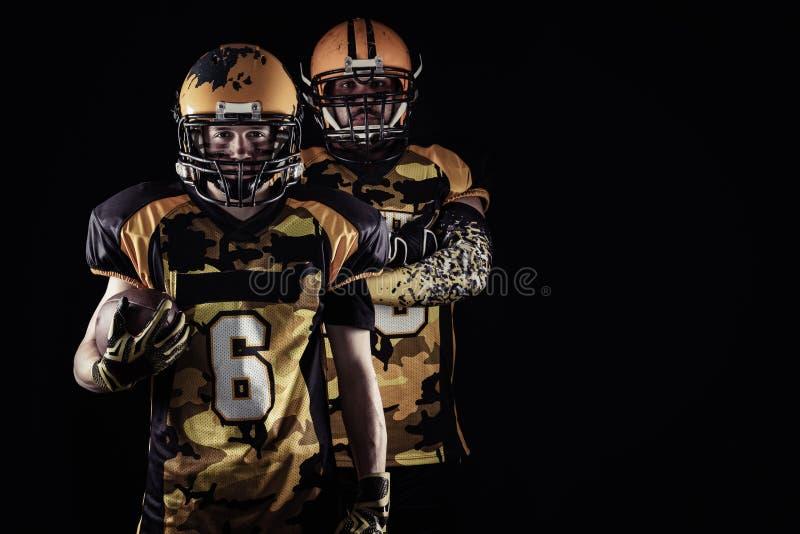 Giocatori di football americano fieri nello scuro fotografie stock