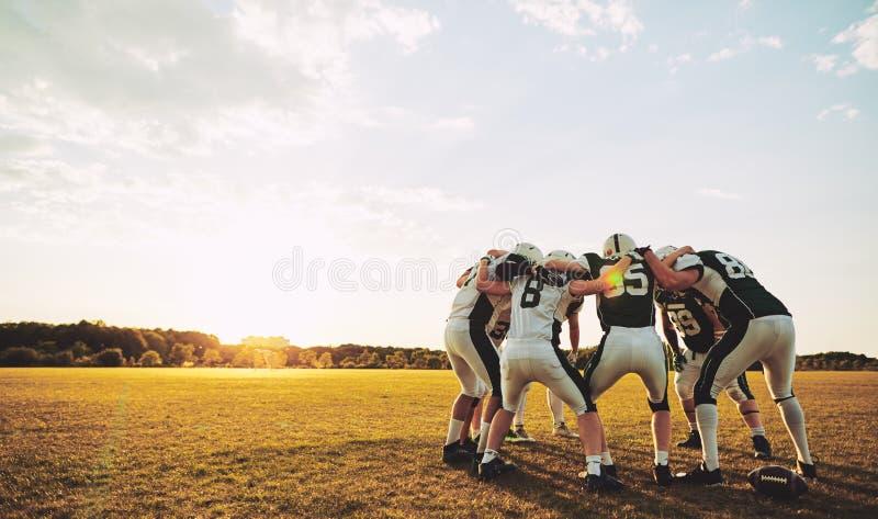 Giocatori di football americano in una calca durante la pratica fotografia stock libera da diritti