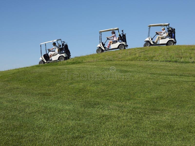 Giocatori di golf che conducono i carretti fotografia stock