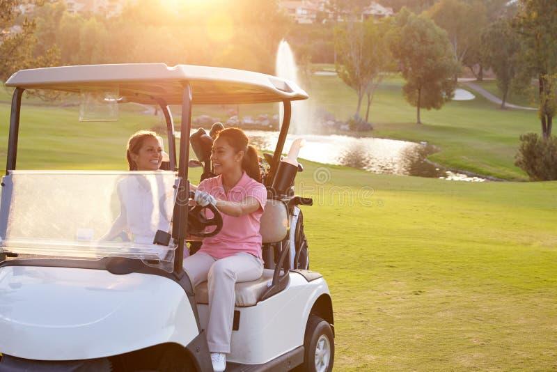 Giocatori di golf femminili che conducono carrozzino lungo il tratto navigabile del campo da golf fotografie stock