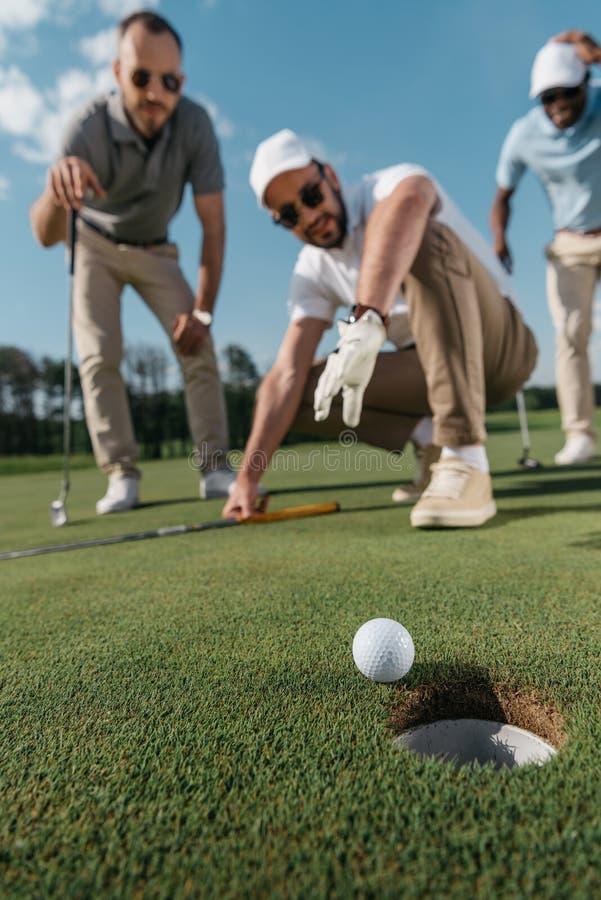 Giocatori di golf professionale che esaminano palla vicino al foro fotografie stock libere da diritti