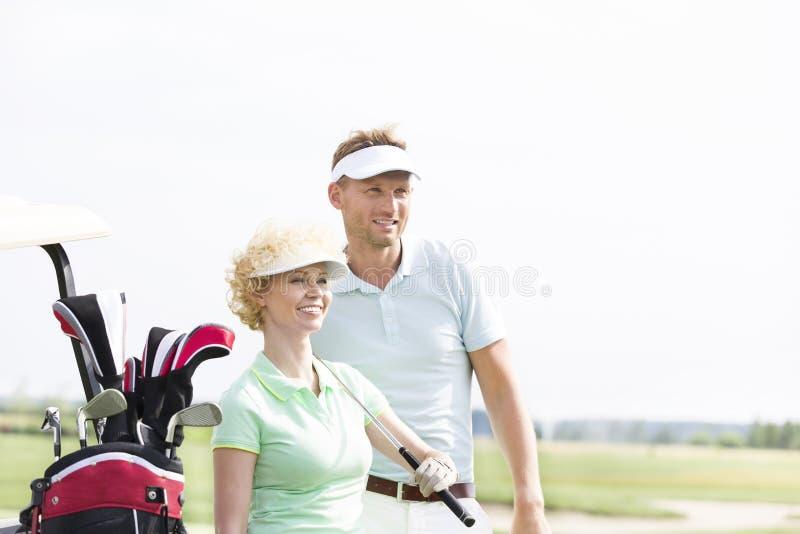 Giocatori di golf sorridenti che stanno al campo da golf contro il chiaro cielo fotografia stock