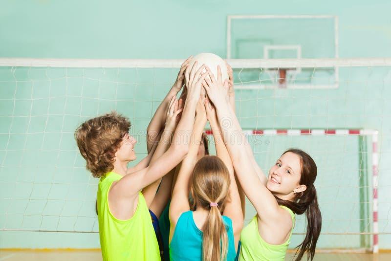 Giocatori di pallavolo adolescenti che giudicano palla sopraelevata immagine stock