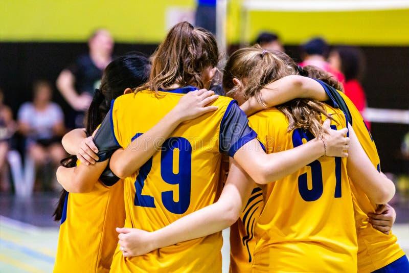 Giocatori di pallavolo femminili che huddling insieme prima dell'iniziare il gioco fotografie stock libere da diritti