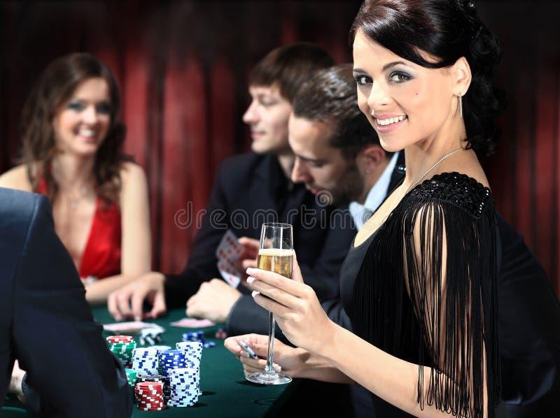 Giocatori di poker che si siedono intorno ad una tavola fotografie stock