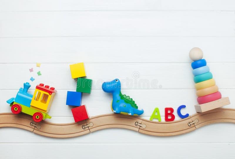 Giocattoli dei bambini sulla ferrovia di legno del giocattolo su fondo di legno bianco con lo spazio della copia immagini stock