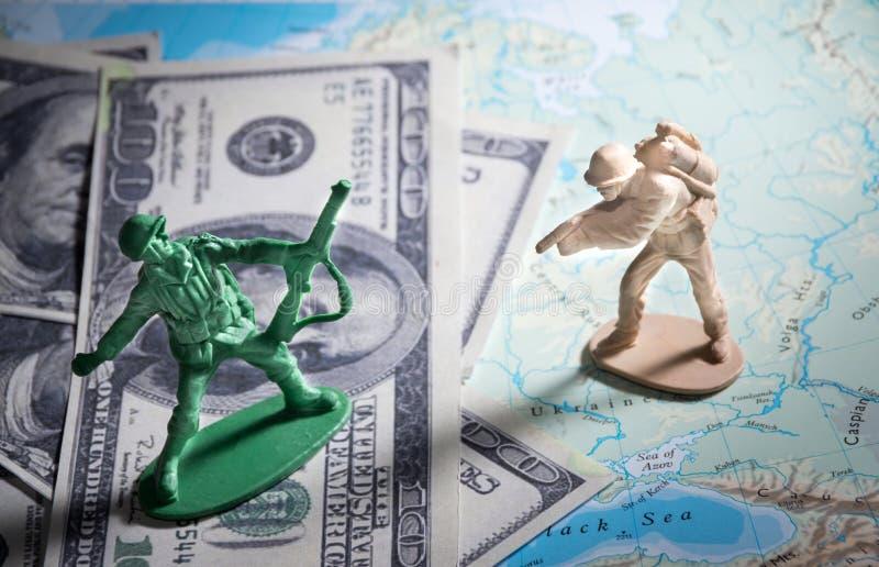 Giocattoli del soldato su soldi e sulla mappa fotografia stock