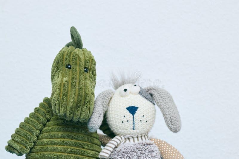 Giocattoli della peluche del dinosauro verde e del coniglio grigio per i bambini su un fondo leggero Vista orizzontale Copi lo sp fotografia stock