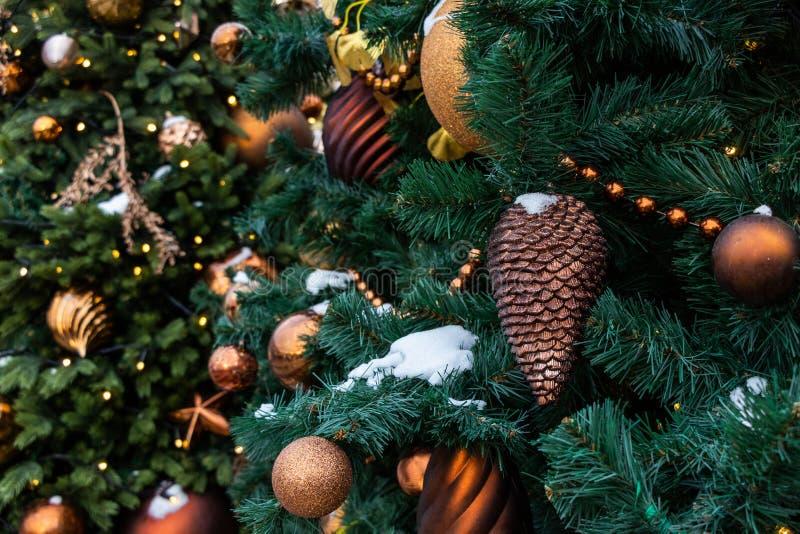 Giocattoli di Natale sull'albero verde con neve Primo piano attillato del cono, palle brillanti dorate Bokeh fotografia stock