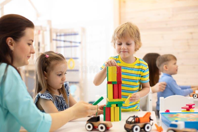 Giocattoli educativi per i bambini di asilo e della scuola materna Bambini svegli che giocano con i blocchi nell'asilo immagine stock