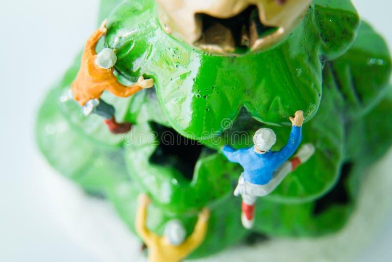 Giocattoli minuscoli che scalano sull'albero di Natale immagine stock