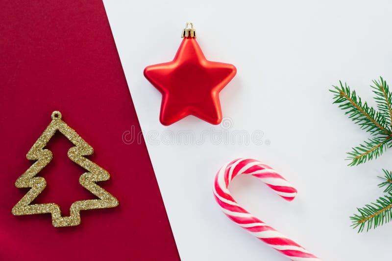 Giocattoli natalizi: stella rossa e albero dorato di Natale, canne lollipop e ramificazioni di abete rosso su uno sfondo diviso i fotografie stock libere da diritti
