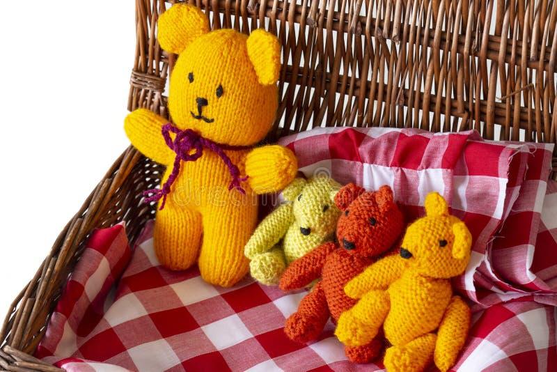 Giocattoli tricottati dell'orsacchiotto sul materiale del tessuto del percalle in un canestro di vimini di picnic fotografia stock