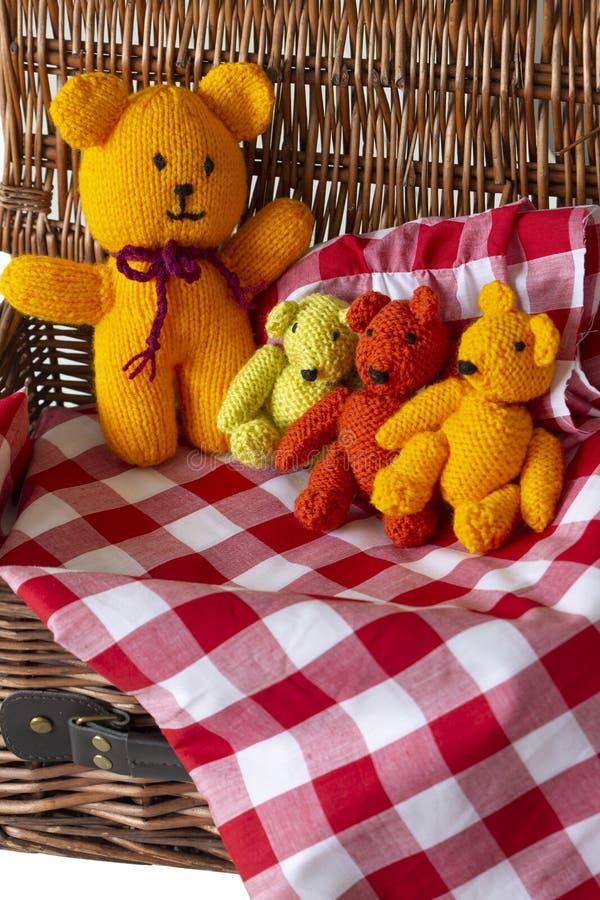 Giocattoli tricottati dell'orsacchiotto sul materiale del tessuto del percalle in un canestro di vimini di picnic fotografia stock libera da diritti