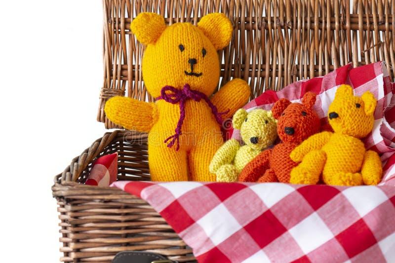 Giocattoli tricottati dell'orsacchiotto sul materiale del tessuto del percalle in un canestro di vimini di picnic fotografie stock