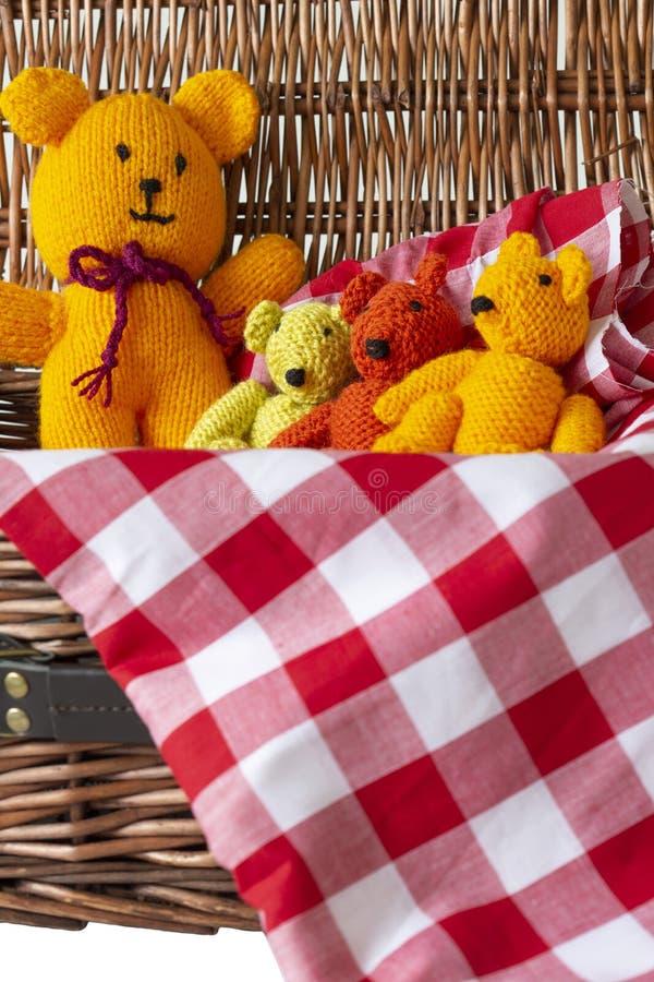 Giocattoli tricottati dell'orsacchiotto sul materiale del tessuto del percalle in un canestro di vimini di picnic immagine stock