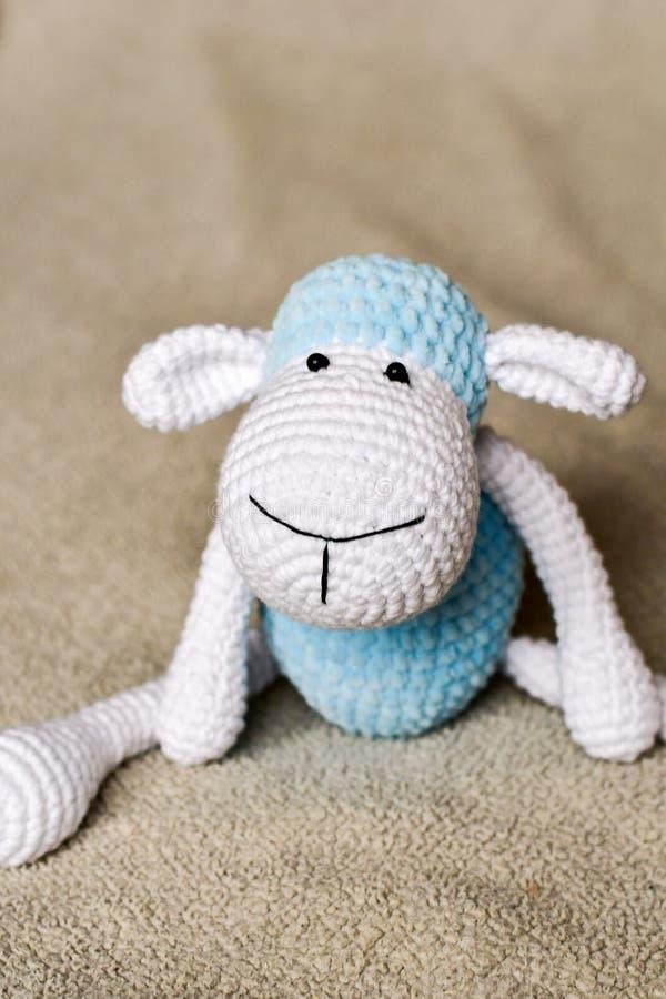 Giocattolo bianco e blu delle pecore al letto fotografia stock