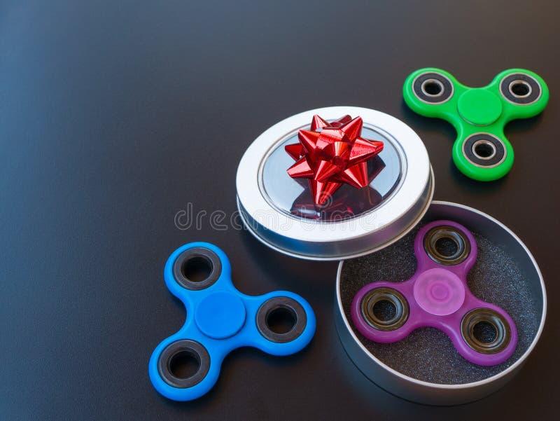 Giocattolo colourful popolare del filatore di irrequietezza in un contenitore di regalo su un fondo nero immagini stock libere da diritti