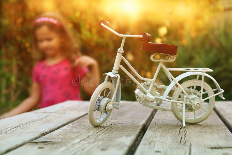 Giocattolo d'annata della bicicletta che aspetta all'aperto nel giardino immagine stock libera da diritti