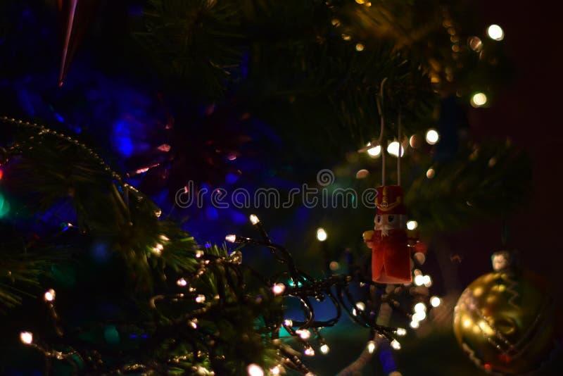 Giocattolo dell'albero di Natale delle schiaccianoci con la palla e le torce elettriche dorate fotografia stock