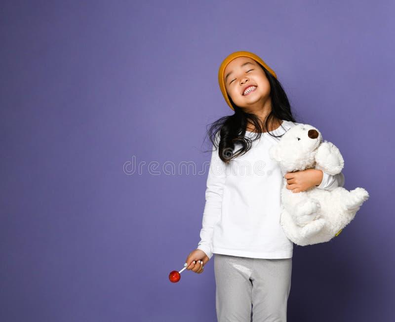 Giocattolo dell'orso polare della tenuta del bambino della ragazza e caramella asiatici di risata sorridenti felici della lecca-l immagine stock libera da diritti