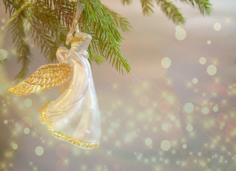 Giocattolo di angelo della tromba di Natale sul ramo dell'albero di Natale su fondo bianco con le luci fotografie stock
